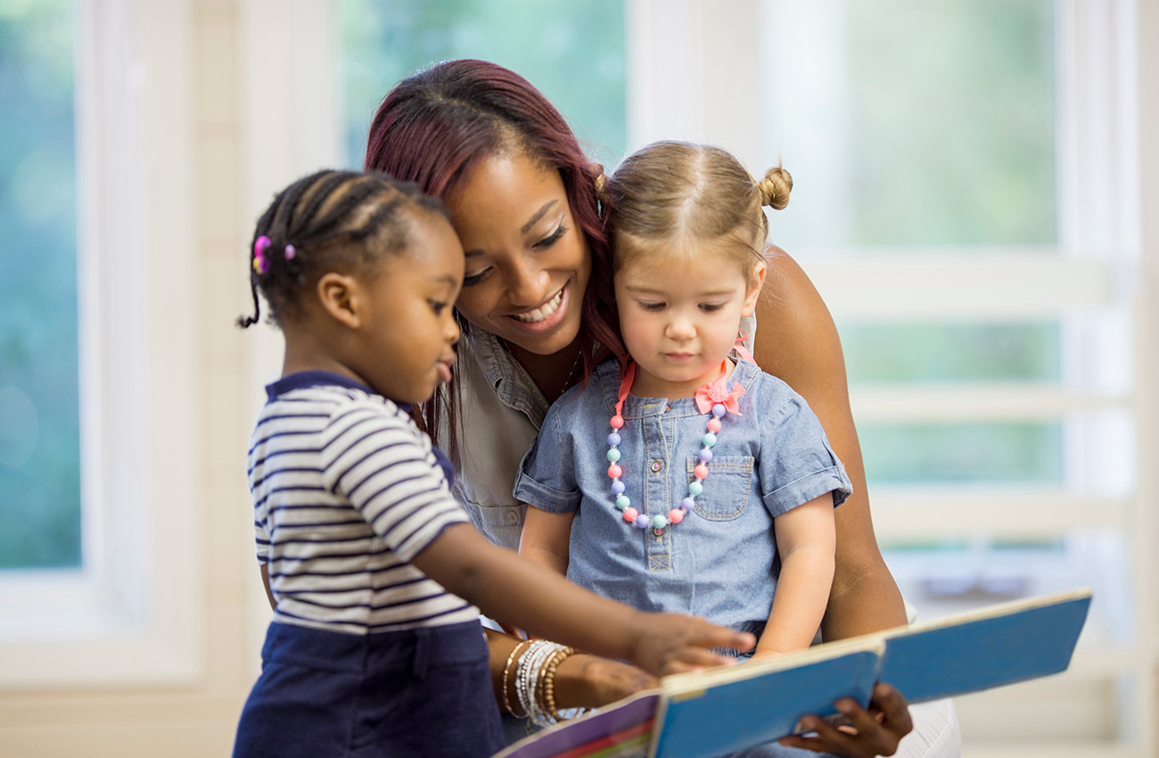 A Child Care Provider Reading Books Together with toddlers