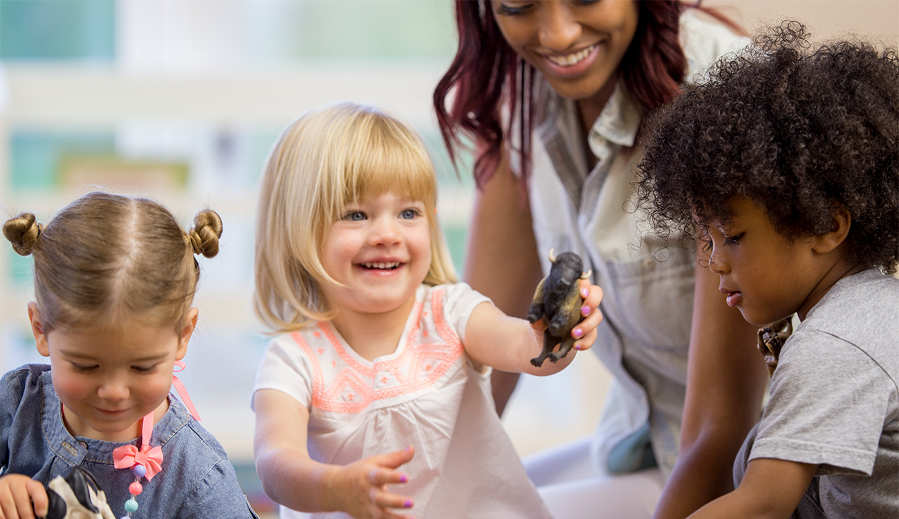 Toddlers sharing toys together with a home child care provider